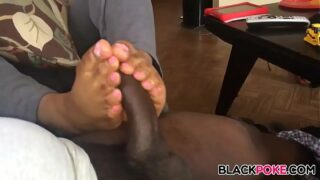 Ebony gives footjob with her pink toes